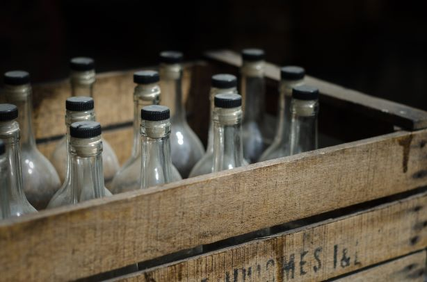 chemistry of rum production. Image shows old bottles in crates.